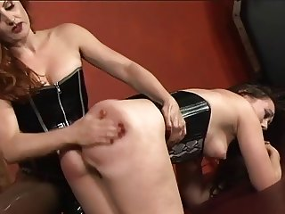 Stunning bdsm lesbians in corsets play with strapons and vibrators in dungeon