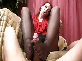 sensual footjob on sofa in black nylons
