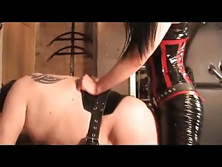 Domina in latex fucks him with strapon