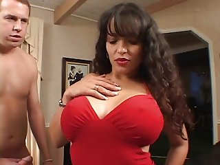 Latina whore with huge fake tits is fucked from behind against chair in hotel
