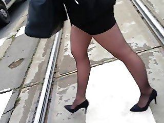 Sheer black pantyhose short skirt high heels.