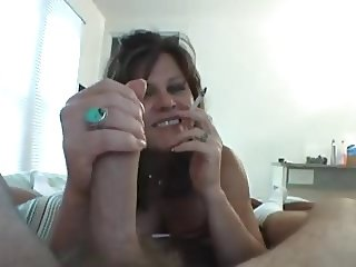 Housewife smoking and gives handjob