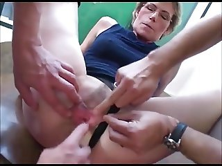 Granny in glasses takes two young cocks