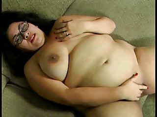 Enormous slut in glasses lays naked on a couch and pleasures herself