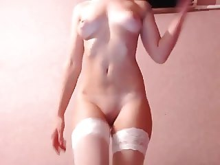 Charming young brunette in white stockings seductively