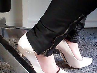 dangling again white high heels under desk